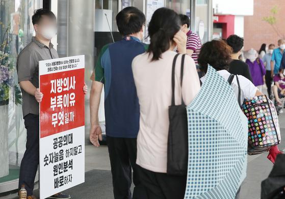전국의사 2차 총파업(집단휴진) 이틀째인 27일 오후 서울 종로구 서울대병원 출입문 앞에서 전공의들이 의대정원 확대 등 정부의 의료정책을 반대하는 손팻말을 들고 있다.  대한전공의협의회(대전협) 등에 따르면 업무개시 명령으로 중앙대병원 전공의 170명, 고려대 안산병원 전공의 149명, 신촌 세브란스 병원 응급의학과 전공의 29명 전원이 사직서를 썼다고 밝혔다. 뉴스1