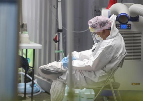 26일 대전시 서구 만년동 서구보건소 코로나19 선별진료소에서 누적된 피로에 지친 한 의료인이 잠시 휴식을 취하고 있다. 연합뉴스