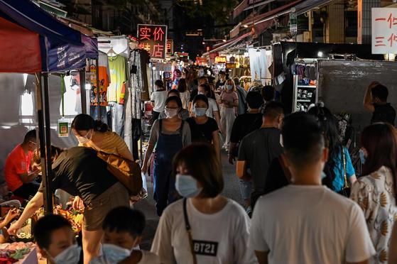 중국 후베이성 우한 야시장을 걷는 사람들. WHO는 전세계로 퍼진 코로나19 기원 조사를 위해 지난달 3주간 중국을 방문했으나 정작 진원지인 우한엔 가지 않고 베이징에만 3주간 머물다 돌아왔다고 밝혀졌다. [AFP=연합뉴스]