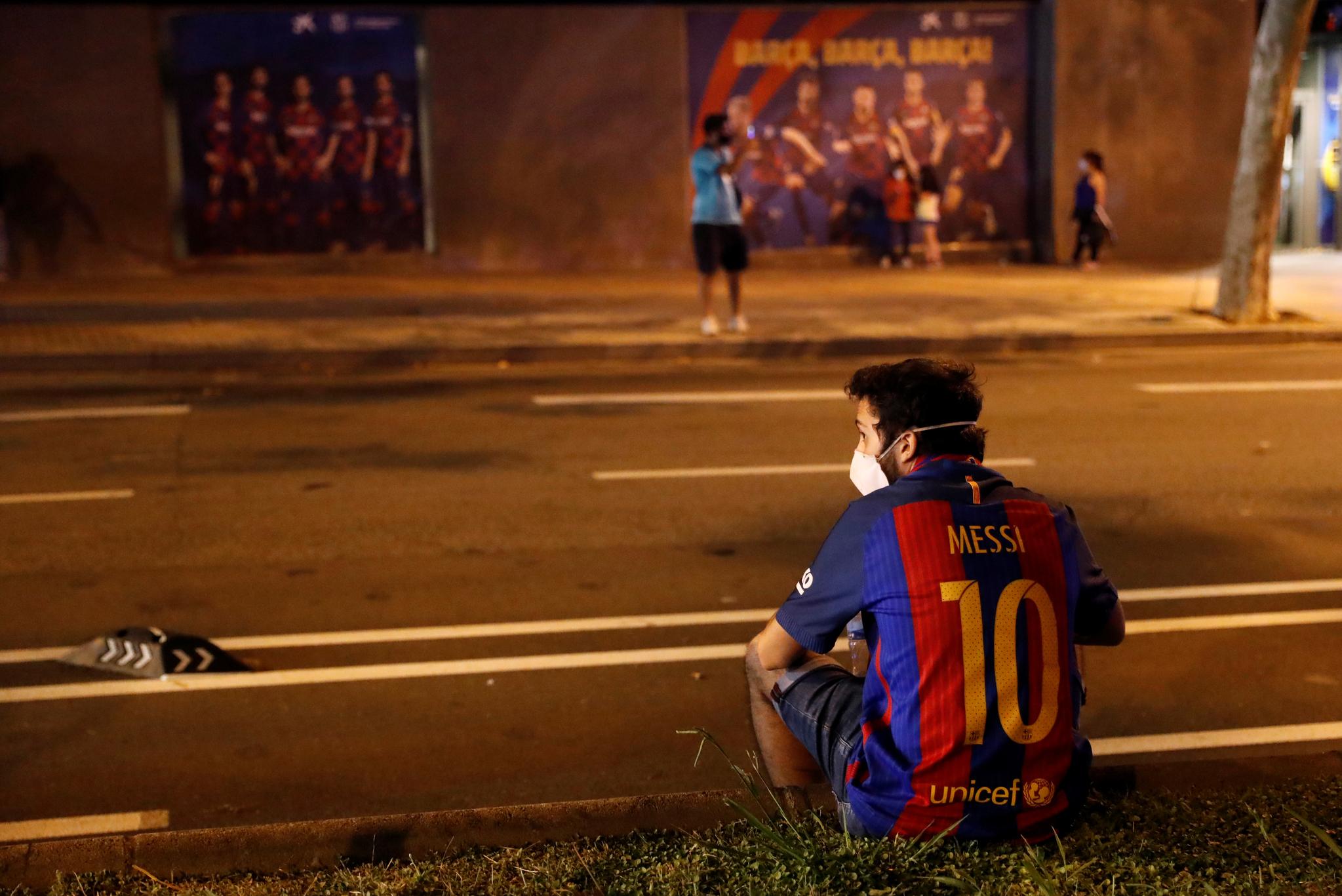 26일(현지시각) 스페인 바르셀로나의 FC 바르셀로나 홈 구장 캄프 누 앞에 리오넬 메시 유니폼을 입은 팬이 마스크를 쓴 채로 도로 중앙분리대에 걸터 앉아 있다. 메시 이적설이 불거지면서 팬들은 구단 측을 비판하는 집단행동에 나섰다. 로이터=연합뉴스