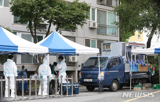 26일 오후 코로나19 집단감염이 발생한 서울 구로구 한 아파트에서 보건소 직원들이 이동형 선별진료소를 설치하고 선별진료, 방역 등을 하고 있다. [뉴시스]