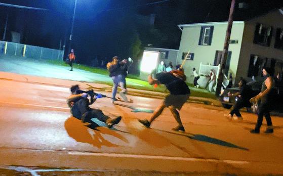 25일 미국 위스콘신주 커노샤에서 소총을 든 남성이 경찰 총격에 치명상을 입은 사건에 항의 시위하는 남성에게 총을 겨누고 있다. SNS에 올라온 동영상을 캡처했다. [로이터=연합뉴스]