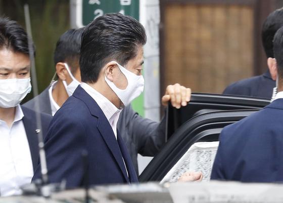 아베 신조 일본 총리는 23 일 도쿄의 미용실에서 헤어 스타일을 마무리하고 차를 쓰고있다. [연합뉴스]