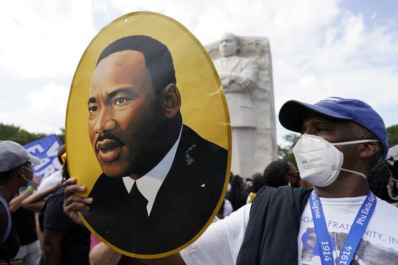 28 일 (현지 시간) '워싱턴 행진'행사에 참석 한 한 남자가 마틴 루터 킹의 초상화를 들고있다. [AP=연합뉴스]