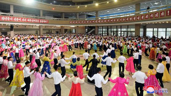 지난 2018년 8월 28일 조선중앙통신이 공개한 사진속에 북한 청년중앙회관 무도회장에서 열린 청년절 경축행사에서 북한 시민들이 다함께 손을 맞잡고 춤을 추고 있다. 조선중앙통신=연합뉴스