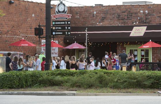 지난 15일 미국 앨라배마 대학 캠퍼스가 위치한 터스컬루사의 한 식당 앞에 사람들이 빽빽하게 모여 있다. 코로나 확진자가 급증하자 시 차원에서 지난 24일부터 식당에서 주류 판매를 보류하라는 명령이 떨어졌다. [AP=연합뉴스]