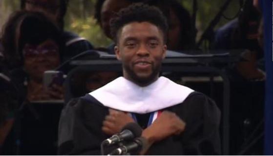 """2018년 5월12일(현지시간) 모교인 워싱턴 하워드대에서 졸업 축사를 마치고 영화 '블랙팬서'의 트레이드마크인 """"와칸다 포에버""""를 변형한 """"하워드 포에버""""를 선사하고 있는 배우 채드윅 보스만. 2016년 대장암을 선고받고 비공개적으로 투병해오다 지난 28일 사망했다. [사진 영상 캡처]"""