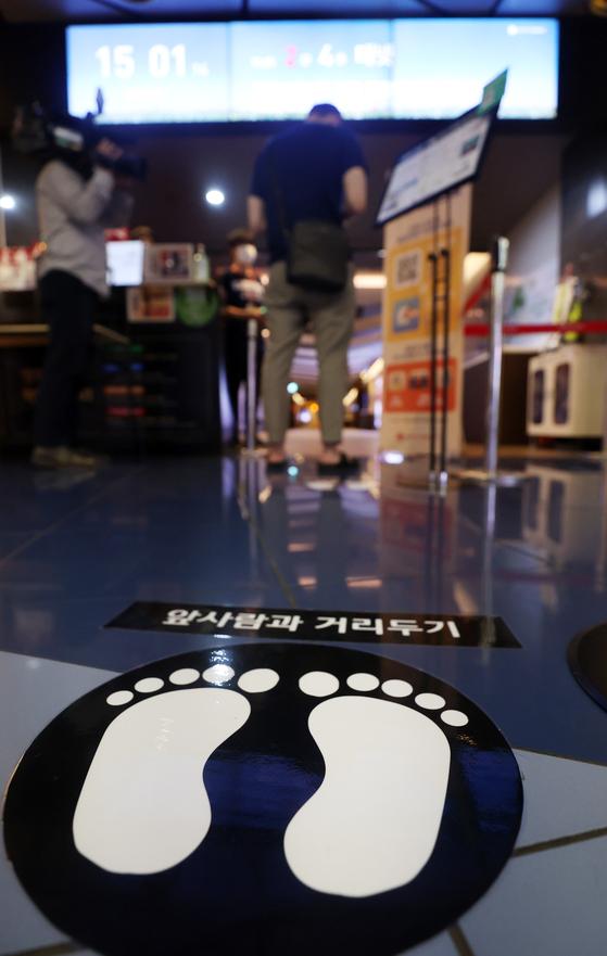 지난 26일 오후 서울시내 한 영화관 상영관 입구 바닥에 거리두기 스티커가 붙어있다. 코로나19로 인해 영화 개봉 공식이 깨지고 안방 관람이 늘면서 OTT 업계와 영화업계 간의 해묵은 지적재산권(IP) 갈등이 표면화하고 있다. [연합뉴스]
