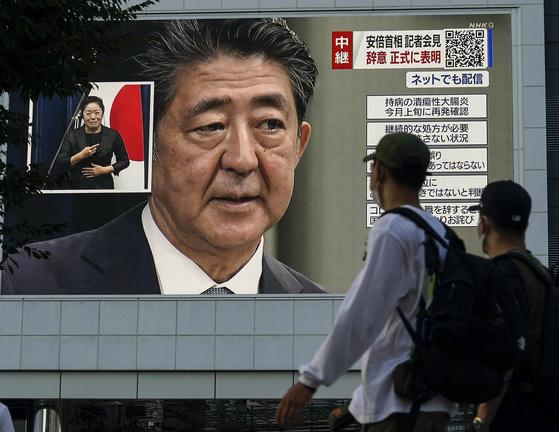 지난 28일 아베 신조 총리의 총리직 사퇴 발표를 TV로 보는 도쿄 시민들. EPA=연합뉴스
