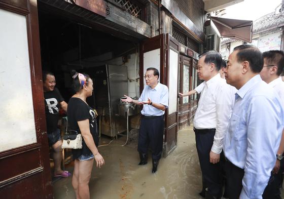지난 20일 리커창(사진 가운데) 중국 총리가 홍수 피해를 입은 충칭을 시찰하고 있다. 리 총리는 장화를 신은 채 흙탕물 속에서 수재민의 의견을 직접 청취했다. [신화=연합뉴스]