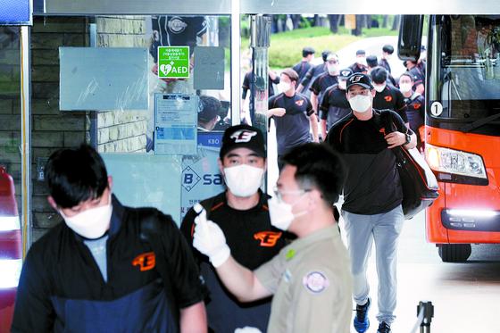 1일 서울 잠실구장에 도착한 한화 선수들이 마스크를 착용한 채 체온 측정을 받은 뒤 입장하고 있다. [뉴스1]