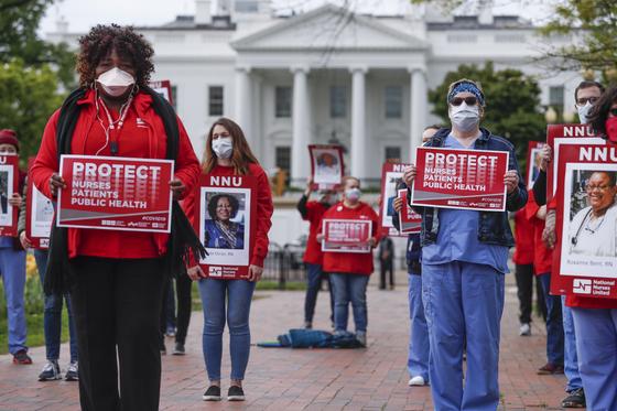 미국 간호사들은 지난 4 월 백악관 앞에서 코로나 19로 사망 한 동료 의료진의 사진을 들고 개인 보호 장비 부족 문제를 해결하기 위해 항의하고 있습니다. [EPA=연합뉴스]