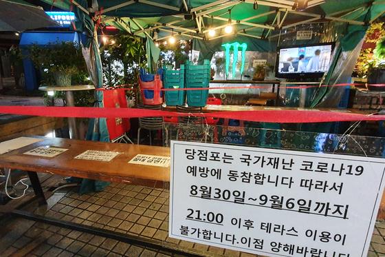 코로나19 확산방지를 위한 수도권 지역의 사회적 거리두기 2.5단계가 시행된 지난달 30일 밤 서울의 한 편의점 간이 테이블 앞에 밤 9시 이후로 이용을 제한한다는 안내문이 붙어 있다. [뉴스1]