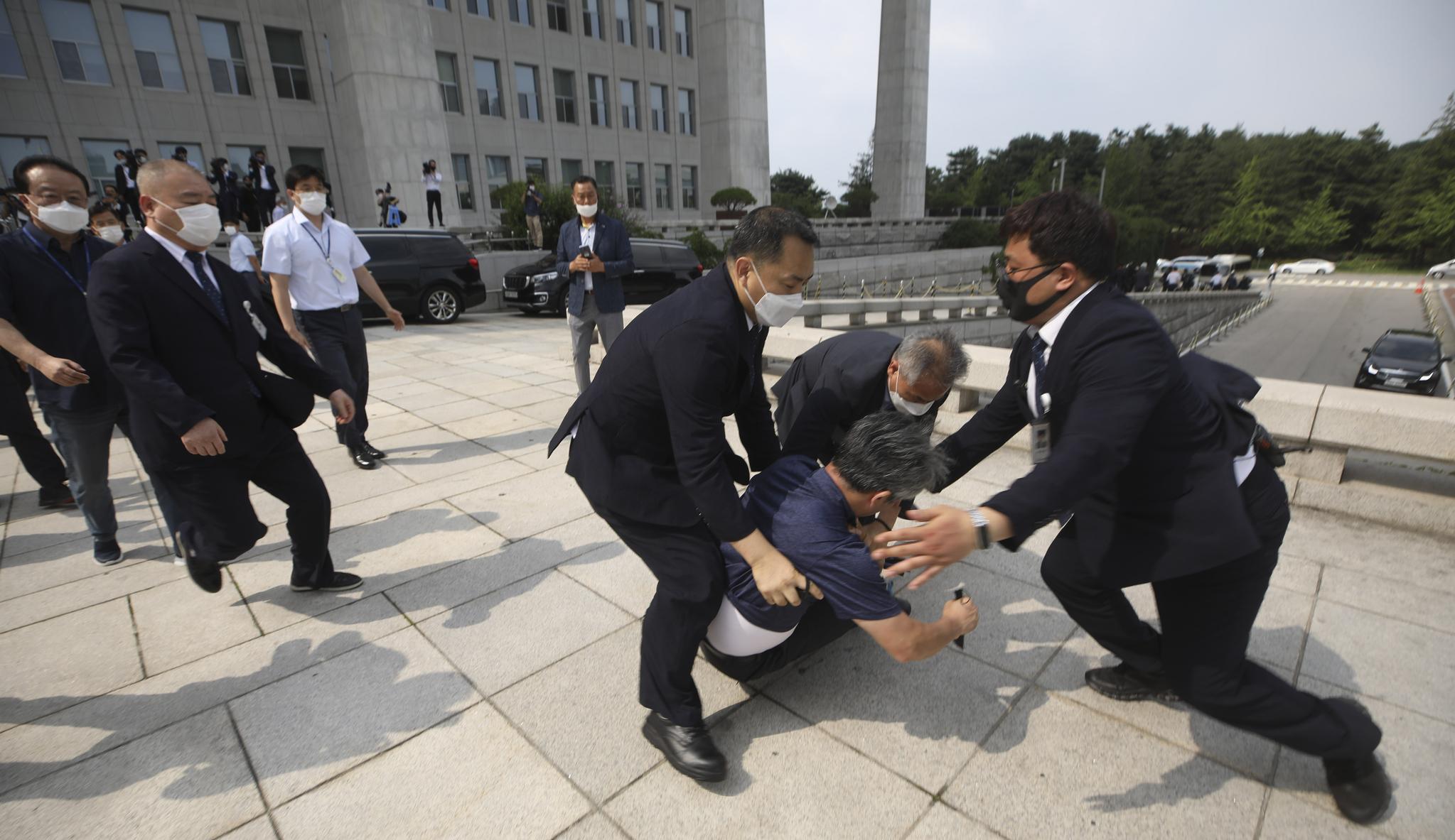 지난 7월 16일 문재인 대통령을 향해 신발을 던진 50대 남성이 경호원들에게 제지당하고 있는 모습. 신발은 문 대통령 근처계단에 떨어졌다. 뉴스1
