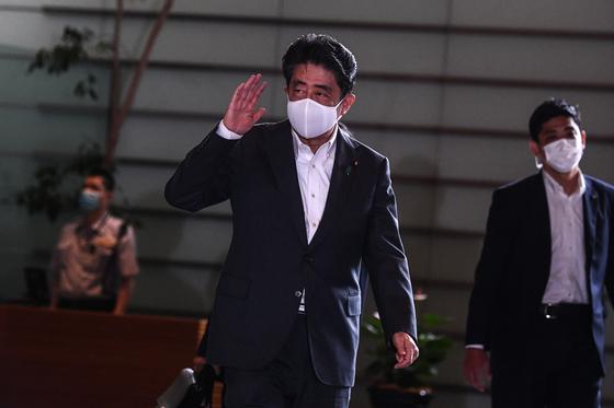 퇴임 의사를 밝힌 아베 신조 일본 총리가 지난달 31일 관저로 출근하며 기자들에게 손을 들어 인사하고 있다. [AFP=연합뉴스]