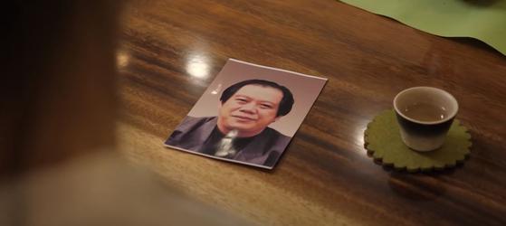 자오 레이가 테이블에 돌아가신 아버지의 사진을 게재 한 채로 스카이 뉴스와 인터뷰하고있다. [유튜브 캡처]
