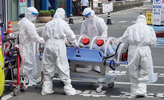 지난달 30일 오후 대구 중구 삼덕동 경북대학교 본원 응급실 앞에 신종 코로나바이러스 감염증(코로나19) 확진자가 이송되고 있다. 연합뉴스