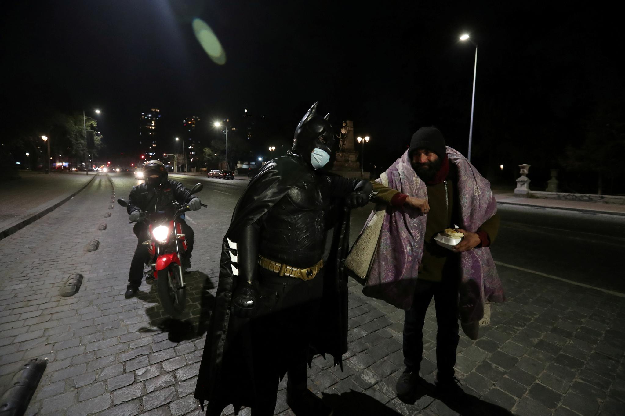 칠레 수도 산티아고에서 가난한 이들을 돕는 '배트맨'이 노숙인과 팔꿈치 인사를 나누고 있다. 로이터=연합뉴스