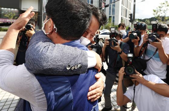 권정오 전국교직원노동조합 위원장(회색 양복)과 김재하 민주노총 비대위원장이 전교조가 승소한 대법원 선고 뒤 대법원 앞에서 열린 기자회견을 마치고 포옹을 하고 있다. [연합뉴스]
