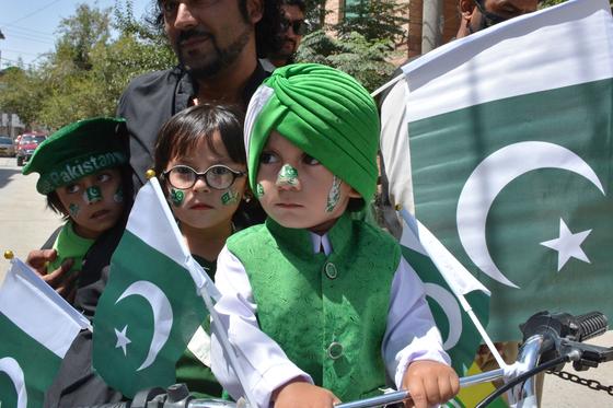 파키스탄 전통 의상을 입고 깃발을 흔들어 아이의 모습 ⓒAFP