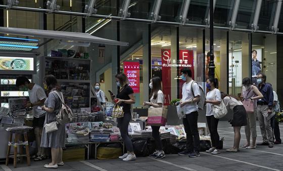 지난달 11일 홍콩 시민들이 반중 성향의 일간지 애플데일리를 사기 위해 줄을 서고 있다. 전날 홍콩 보안법 저촉 혐의로 체포된 지미라이 사주를 지지하는 시민의 성원으로 평소 7만여부 팔리던 신문이 이날 55만부 판매됐다. [AP=연합뉴스]