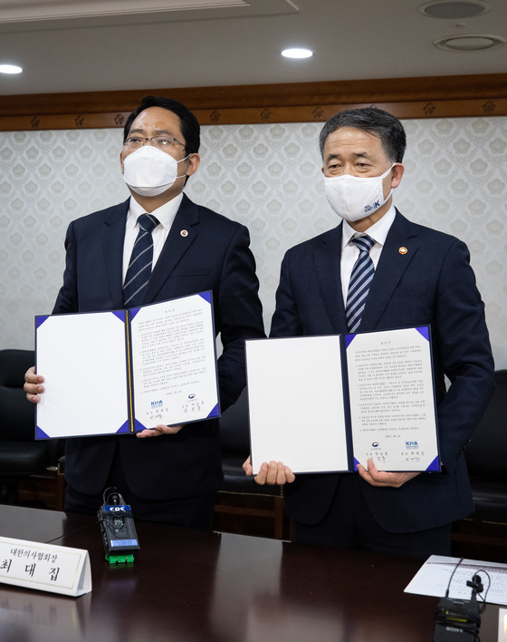박능후 보건복지부 장관(오른쪽)과 최대집 대한의사협회장은 4일 서울 종로구 정부서울청사에서 집단휴진을 중단하고 의대정원 확대 등의 의료정책을 협의하는 의정협의체를 구성하는 내용에 합의했다. 뉴스1