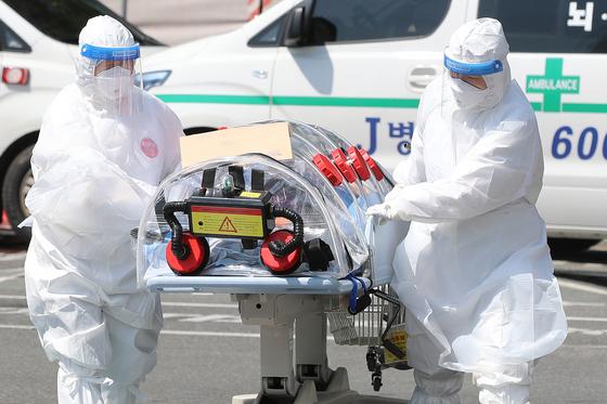 4일 오전 대구 중구 삼덕동 경북대학교병원에서 의료진이 119구급대 의해 이송된 신종 코로나바이러스 감염증(코로나19) 확진 환자를 음압형 환자 이송장치를 이용해 옮기고 있다. 뉴스1