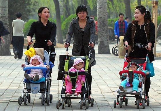 중국 도시 지역을 중심으로 아이가 즈루이루 경우 한 명의 아버지를 더 한 어머니를 붙여 준다 경우가 늘고있다.  사진은 베이징의 공원에 나온 여성이 아이를 태운 유모차를 끌고있는 모습 [AFP=연합뉴스]