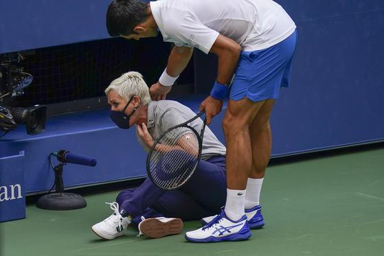 7일 조코비치가 자신의 분노샷에 공을 맞고 쓰러진 선심에게 달려가 상태를 살피고 있다. [AP=연합뉴스]