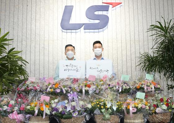 구본혁 예스코홀딩스 부사장(왼쪽)과 구동휘 (주)LS 전무가 7일 LS용산타워에서 '플라워 버킷 챌린지'에 동참하고 기념사진을 촬영하고 있다. 사진 LS