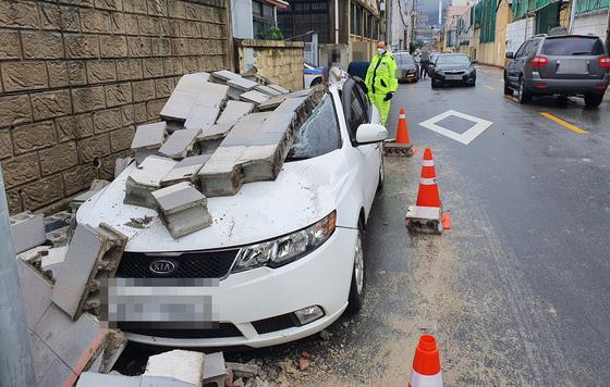 7일 오전 제10호 태풍 하이선의 북상으로 부산 영도구 한 건물 벽면이 무너지면서 주차된 차량이 파손돼 있다. 인명 피해는 없었다. 연합뉴스