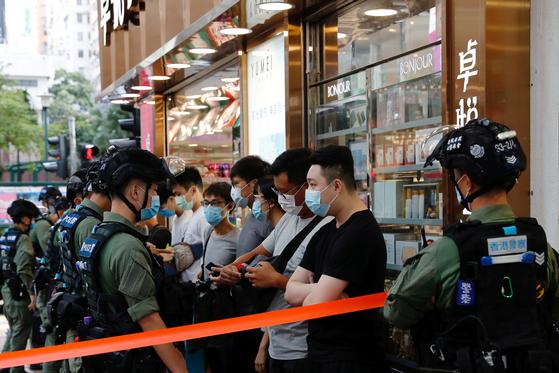 6일(현지시간) 홍콩에서 현지 경찰들이 시민들에게 신분증 제출을 요구하고 있다. [로이터=연합뉴스]