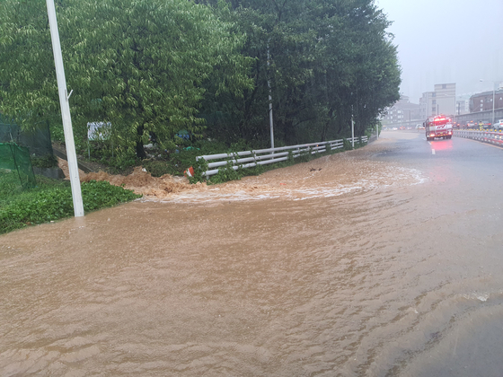 7일 오전 8시 30분 부산 북부 광덕물산 앞 토사가 유출하면서 흙탕물이 도로 위로 쏟아지고 있다. [사진 부산경찰청]
