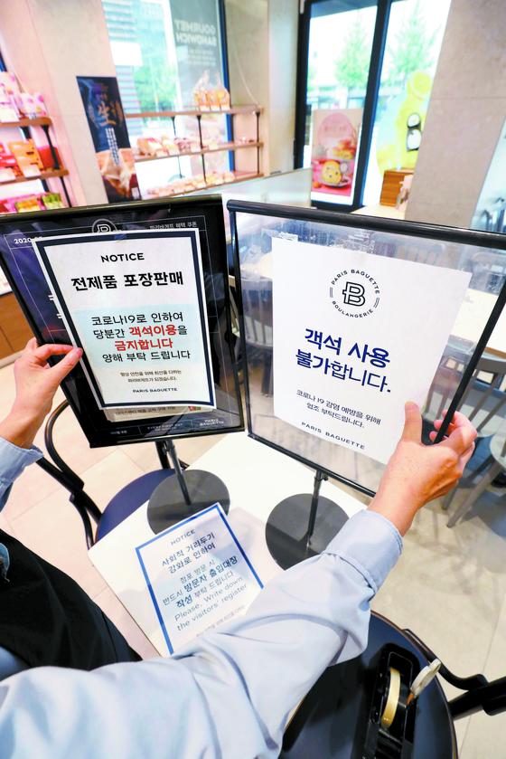 6일 서울의 한 프랜차이즈형 제과점에서 직원이 안내문을 부착하고 있다. 정부의 방역 지침에 따라 7일부터 프랜차이즈형 제과제빵·아이스크림·빙수점에서도 매장 내 취식이 금지된다. [뉴스1]