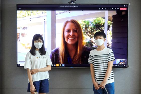 박지민(왼쪽) 학생기자와 이주영 학생모델이 원격회의 시작 전 퀘른스트롬 매니저와 사진을 촬영했다.