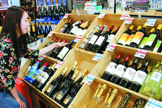 코로나19 확산에도 캠핑과 홈파티가 늘며 와인 판매는 증가하고 있다. 한 대형마트에서 고객이 와인을 고르고 있다. [연합뉴스]