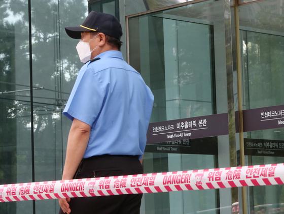한 경비원이 건물 출입을 통제하고 있다. 기사 내용과 관련 없음. 연합뉴스