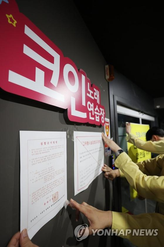 노래방에 집합금지명령문을 붙이고 있는 모습. 춘천시에서는 영업을 못한 고위험시설에 긴급재난지원금 100만원 지급을 추진하고 있다. [연합뉴스]