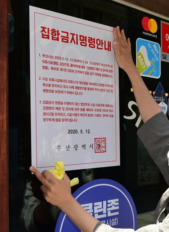 지난 5월 12일 부산 부산진구 공무원들이 서면 일대 유흥시설에 집합금지 행정명령서를 부착하고 있다. 송봉근 기자