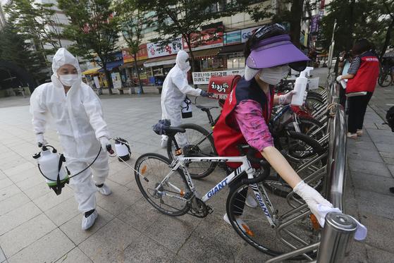 한국에서 코로나19 예방을 위해 방역 근로자와 자원봉사자들이 공원 시설을 소독하고 있다. [AP=연합뉴스]