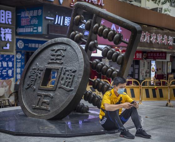 '디지털 화폐-전자 결제'(DCEP·Digital Currency Electronic Payment)로 표기하는 중국 인민은행이 발행한 디지털 위안화가 중국에서 시범 운영을 시작했다. 코로나19로 언택트 경제 발전이 빨라지면서 세계적으로 디지털 화폐 도입 속도가 빨라지고 있다. 중국 광저우 도심에 위안화를 상징하는 조형물 옆에 마스크를 쓴 시민이 휴대폰을 사용하고 있다. [EPA=연합뉴스]