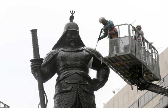 작업자들이 크레인에 올라가 이순신 장군 동상에 분사기로 물을 뿌리며 세척작업을 벌이고 있다. 김상선 기자