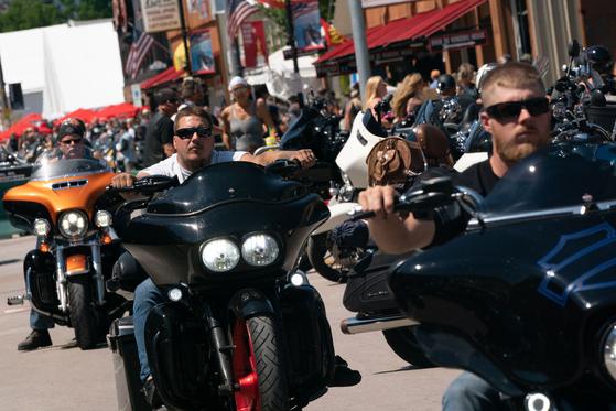 지난달 8일 미국 사우스다코타주 스터지스에서 열린 '스터지스 모터사이클 랠리' 참가자들이 마스크도 쓰지 않은 채 할리데이비슨 오토바이를 타고 행진하고 있다. [AFP=연합뉴스]