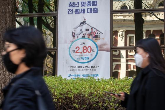 서울시내 한 은행에 걸린 대출광고 앞을 시민들이 지나고 있다.뉴스1