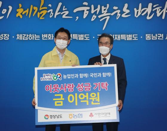 이성희 농협중앙회장(오른쪽)이 9일 경남도청에서 김경수 경남지사와 만나 '이웃사랑 성금' 2억원을 기탁했다. 사진 농협