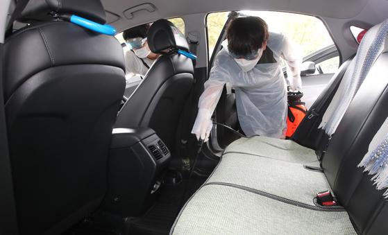 8일 부산 동구 부산역 앞 택시승강장에서 택시방역소 방역요원들이 정차중인 택시에 소독을 실시하고 있다. 부산시의 코로나19 극복 희망일자리사업과 연계한 생활 방역 강화를 위한 이 방역사업은 11월말까지 계속된다. 송봉근 기자