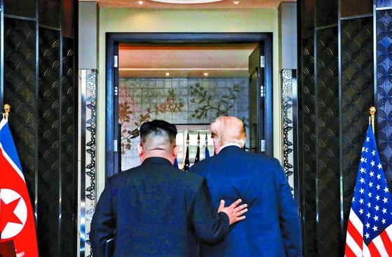 김정은 북한 국무위원장(왼쪽)과 도널드 트럼프 미국 대통령이 12일(현지시간) 싱가포르의 카펠라 호텔에서 북·미 정상회담 공동성명 문서에 서명을 마치고 이동하고 있다. [신화사]