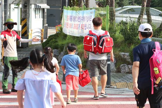지난달 24일 오전 한 초등학교 앞에서 학부모가 자녀의 가방을 메고 함께 횡단보도를 건너고 있다. 뉴스1