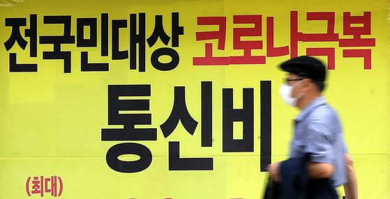 14일 서울시내의 한 통신사 매장 앞으로 시민이 지나가고 있다. [뉴스1]