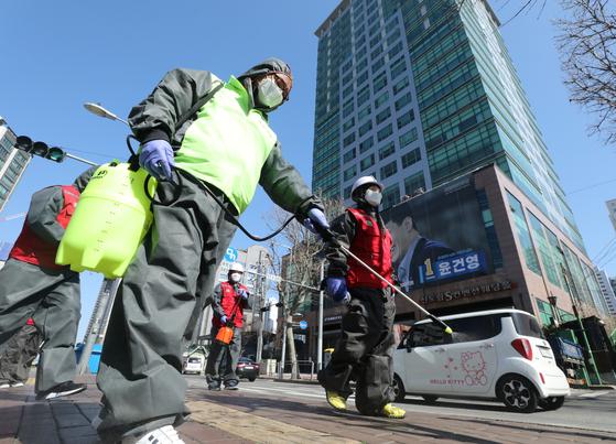 서울 구로구 콜센터에 발생한 신종 코로나바이러스 감염증(코로나19) 확진자가 90명으로 늘어난 지난 3월 11일 빌딩 앞 버스정류장에서 구로구시설관리공단 관계자들이 방역 작업을 하고 있다. 뉴스1